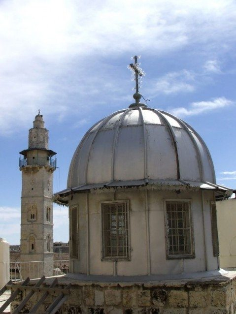 Kisha e Varrit të Shenjtë, mbrapa së cilës shihet minarja katrore e xhamisë së Hazret Omerit.